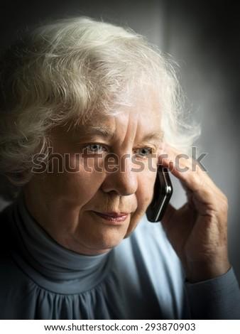 Sad senior caucasian woman speaks by cell phone - stock photo