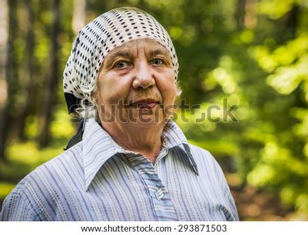 Sad senior caucasian woman with kerchief outdoor - stock photo