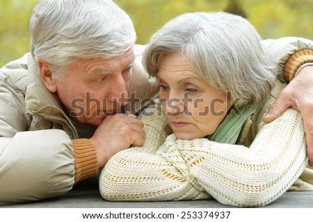 Sad senior couple in autumn park - stock photo