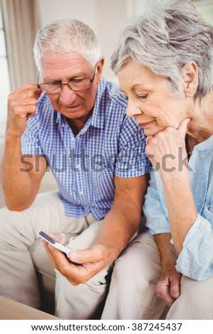 Sad senior couple sitting on sofa and looking at mobile phone in living room - stock photo