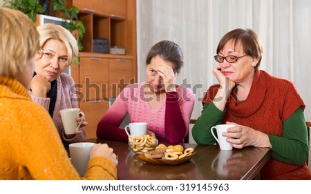 sad senior female friends drinking tea and sharing problems at table  indoor - stock photo