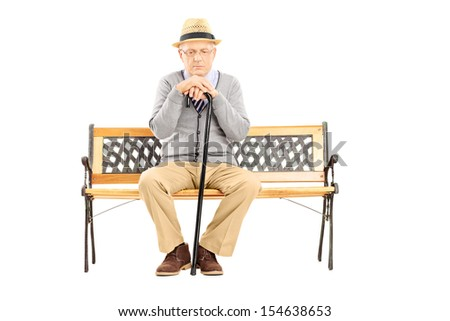 Sad senior man with a cane sitting on a wooden bench isolated on white background - stock photo