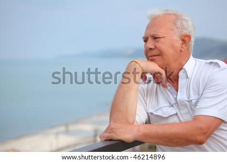 sad senior on veranda near seacoast, looking afar, lean elbows about handrail - stock photo