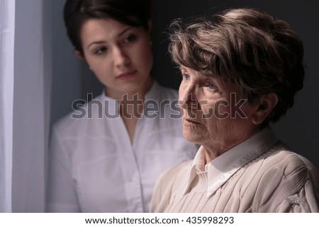 Sad senior woman and good, young carer. - stock photo