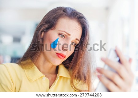 "Sad smiley concept. woman with ""emoji"" style tear of her sad face - stock photo"