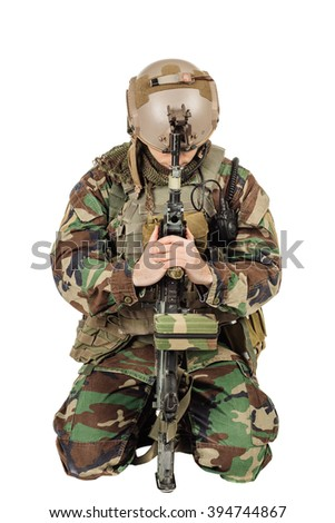 Sad Soldier In Uniform Praying and sitting with a gun - stock photo