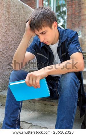 Sad Student with the Book on the landing steps - stock photo