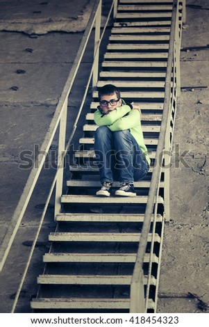 Sad teen boy in depression sitting on the steps  - stock photo