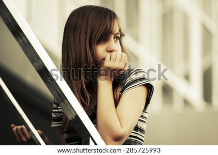 Sad teen girl against a school building  - stock photo