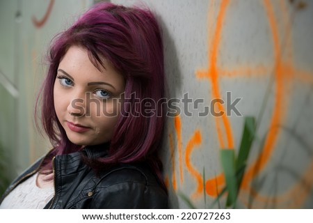 Sad teen girl leans up against graffiti covered wall outside school - stock photo