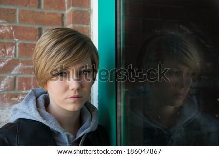 Sad teen girl outside school, with reflection from door window - stock photo