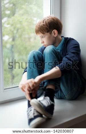 Sad teen sitting on window - stock photo
