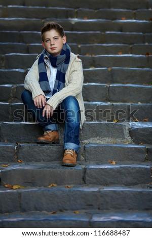 sad teenage boy sit on stone stairs outdoor - stock photo
