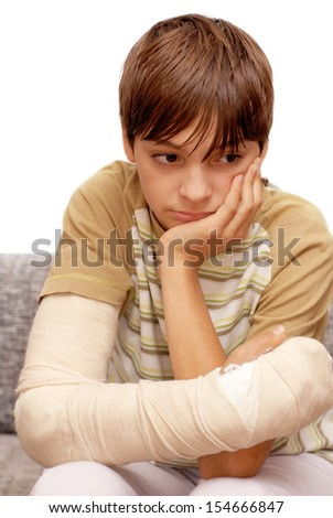 sad teenage caucasian boy with broken arm bone - stock photo