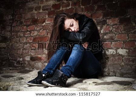Sad teenage girl, leaning on an old brick wall. - stock photo