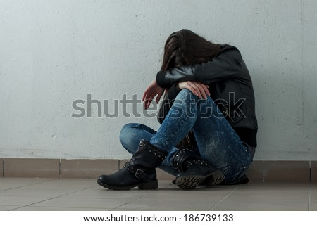 Sad teenage girl with hands over face. - stock photo