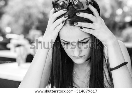 sad teenage woman sitting , she is touching head, black and white photography - stock photo