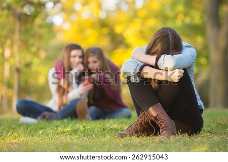 Sad teenage woman sitting with head down near laughing group - stock photo