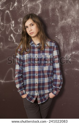 sad teenager girl in chequered shirt and jeans standing near brown wall - stock photo