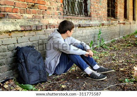 Sad Teenager near the Brick Wall of the Old House - stock photo