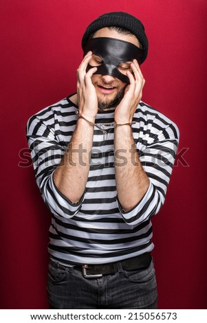 Sad thief with handcuffs. Portrait on red background   - stock photo