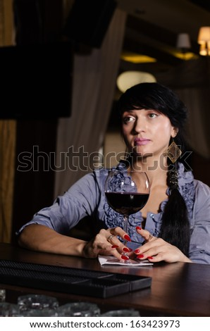 Sad thoughtful attractive young woman drinking at the pub enjoying a large glass of red wine as she sits at the counter staring into space - stock photo