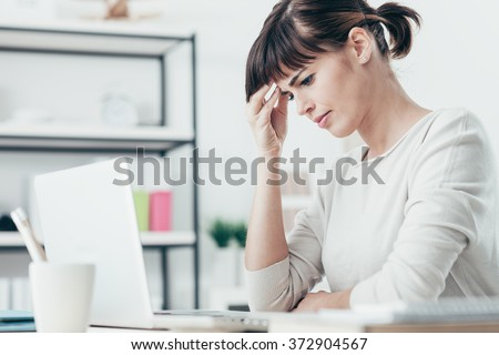 Sad tired woman having a bad headache, she is sitting at office desk and touching her temple - stock photo