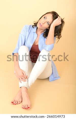 Sad Unhappy Worried Attractive Beautiful Young Woman Sitting on the Floor Wearing a Blue Shirt and White Jeans - stock photo
