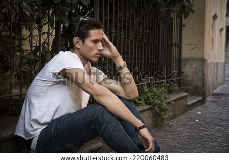 Sad, unhappy young man outdoor, sitting on pavement, holding head with his hand - stock photo
