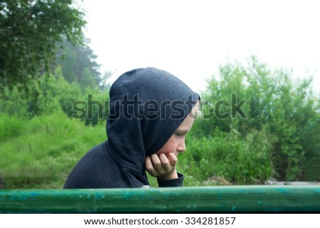 Sad upset abused teenager (boy, kid) sitting alone on bench in park outdoor - stock photo