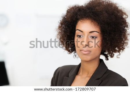 Sad wistful African American businesswoman staring downwards with a calm withdrawn expression, head and shoulders portrait on white - stock photo