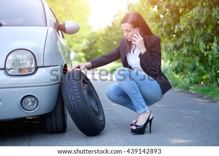 Sad woman calling assistance service  after unexpected vehicle breakdown - stock photo