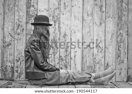 Sad woman deep in thought sitting over grunge wooden background. black and white - stock photo