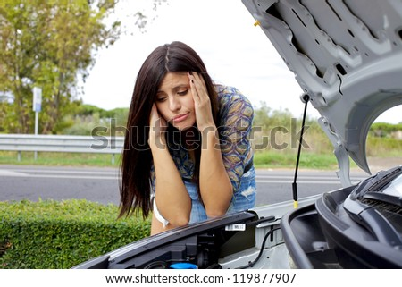 Sad woman depressed not knowing what to do with broken car - stock photo