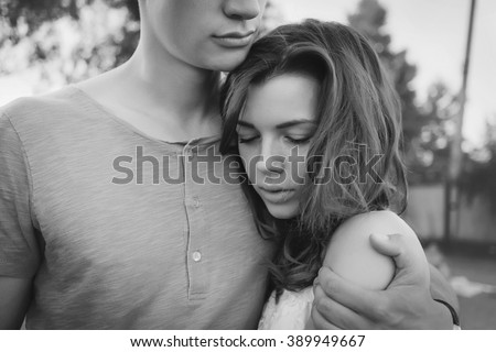 Sad woman hugging her boyfriend and looking down couple problems concept black and white - stock photo