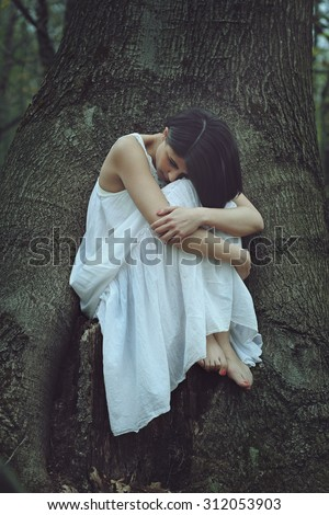 Sad woman in a forest. Loneliness and melancholy concept - stock photo