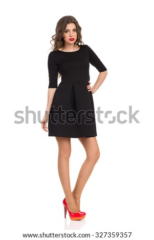 Sad woman in black mini dress and red high heels standing and holding hand on hip. Full length studio shot isolated on white. - stock photo