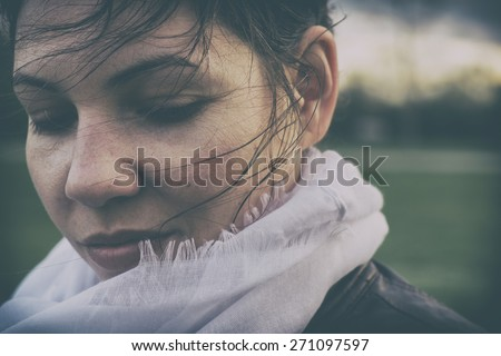 Sad woman in windy weather. Analog effected photo - stock photo