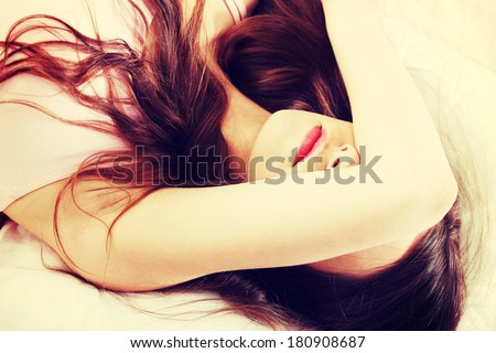 Sad woman is lying in bed with her arm on head and eyes. Young woman with long hair, wears pink underwear. - stock photo