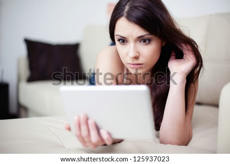 Sad woman lying on couch with tablet - stock photo