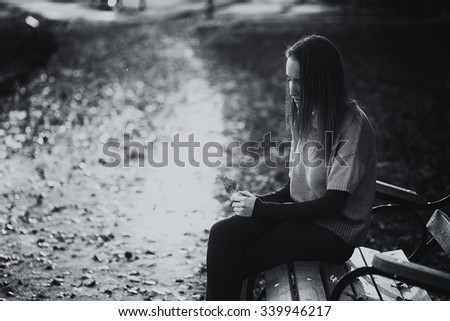 Sad woman on a bench in the park - stock photo