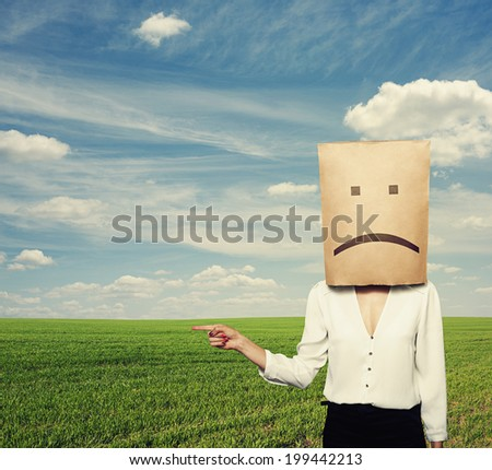 sad woman pointing at something over green field - stock photo