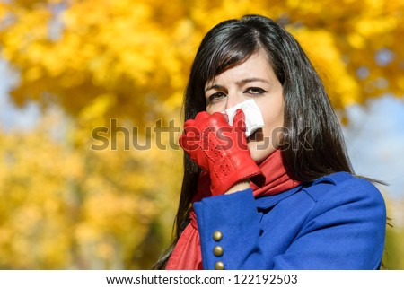 Sad woman sick with the flu or cold blowing the nose with a handkerchief in autumn season. Autumnal illness. - stock photo