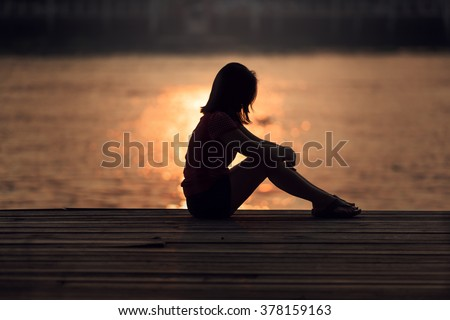 Sad woman silhouette worried at sunset - stock photo