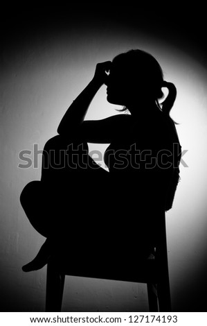 sad woman sitting alone - black and white - stock photo