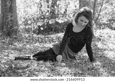 Sad woman sitting alone in the forest. - stock photo