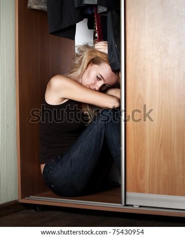 Sad woman sitting in the closet - stock photo