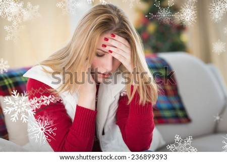 Sad woman sitting in the living room on a couch against snowflakes - stock photo