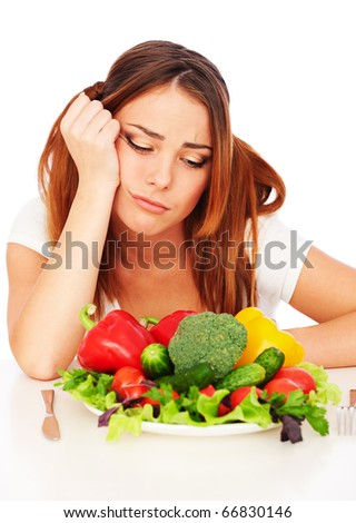 sad woman sitting near plate with vegetables and tired from diet - stock photo