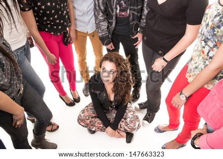 Sad woman sitting on a floor in the middle of a group, studio shot - stock photo